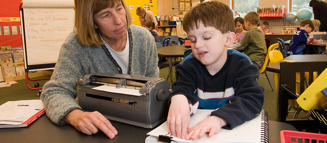 A teacher and student have a braille lesson